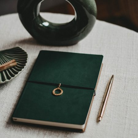 journal writing prompts - Green journaling book and pen